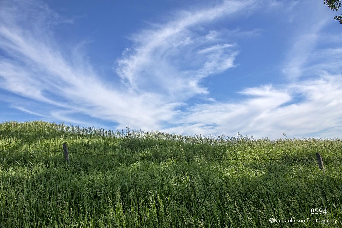 landscape field grasses fence clouds