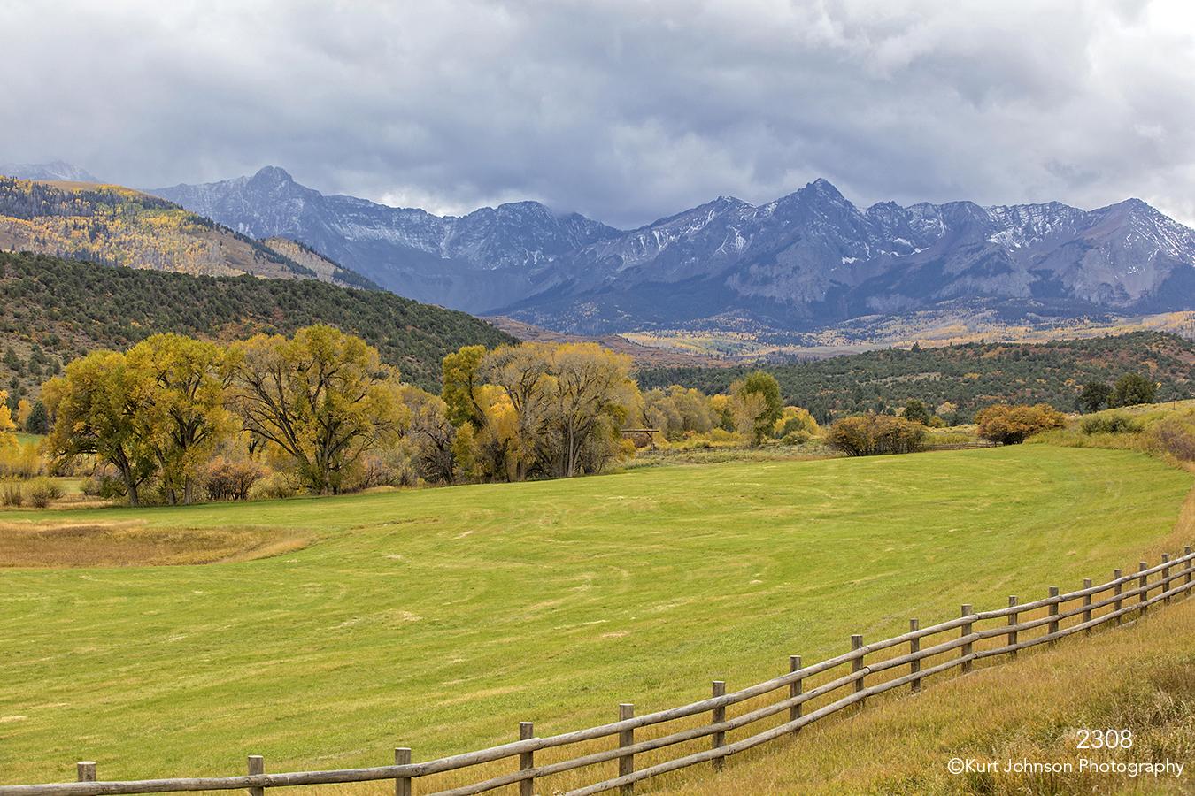 landscape mountains fence trees clouds colorado grasses