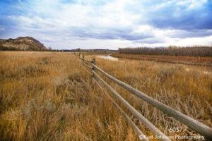 landscape grasses fence clouds river trees earthtones mountains dakota midwest