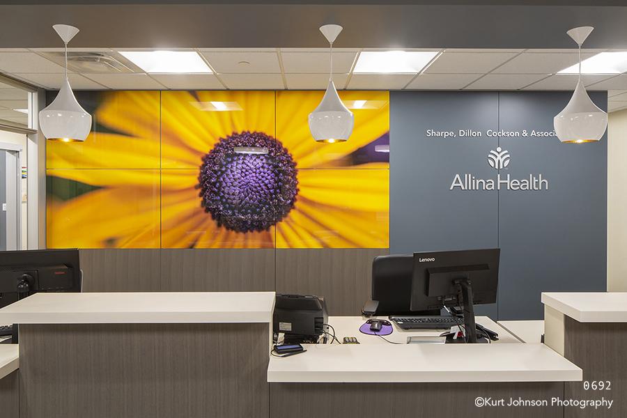 Allina Health art install yellow flower front desk healthcare installation design