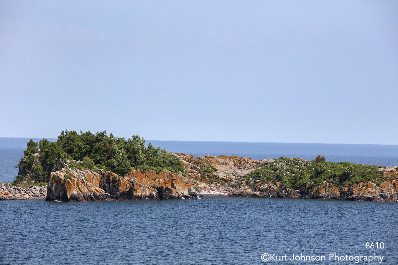 water waves river ocean rock stone trees bushes green blue brown waterscape horizon