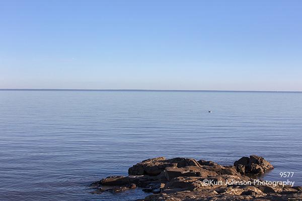 rock stone ocean waves blue shore horizon brown water waterscape