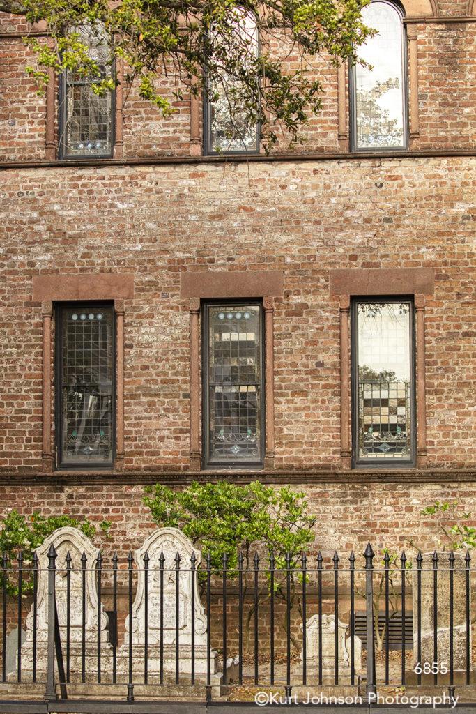 southeast Charleston South Carolina green trees red brick architecture building black gate fence windows city