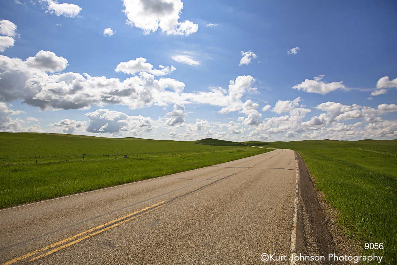 midwest road yellow lines path blue sky clouds green grass country landscape