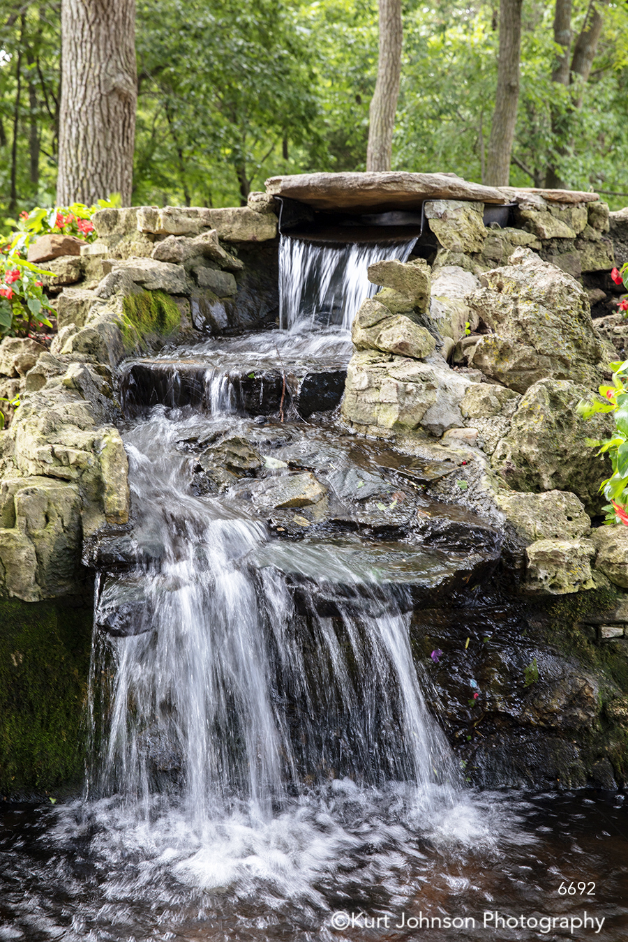 running water waterfall stream brown rocks green grass grasses flowers waterscape