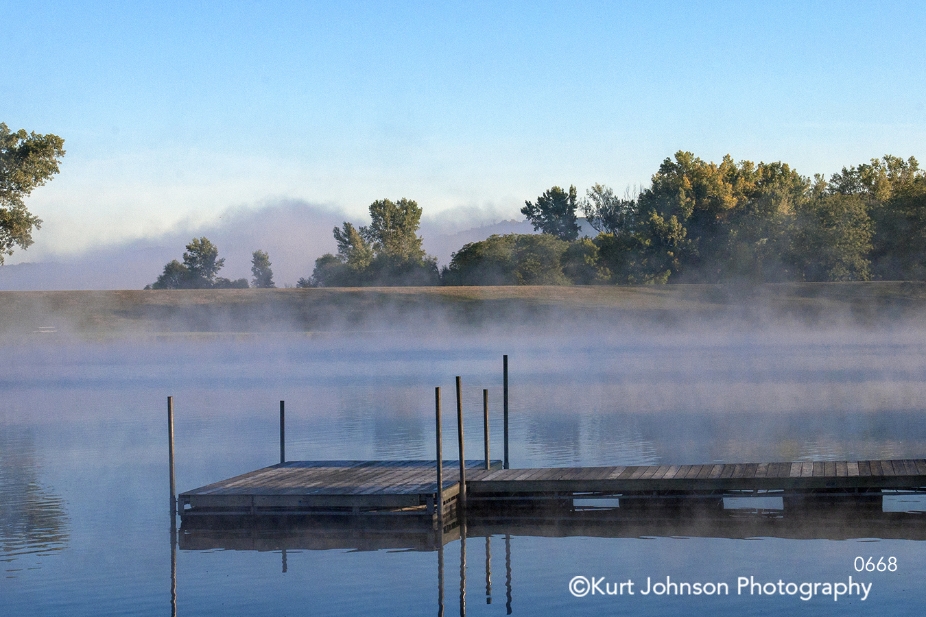 blue calm water edge shore dock fog waterscape trees sky horizon