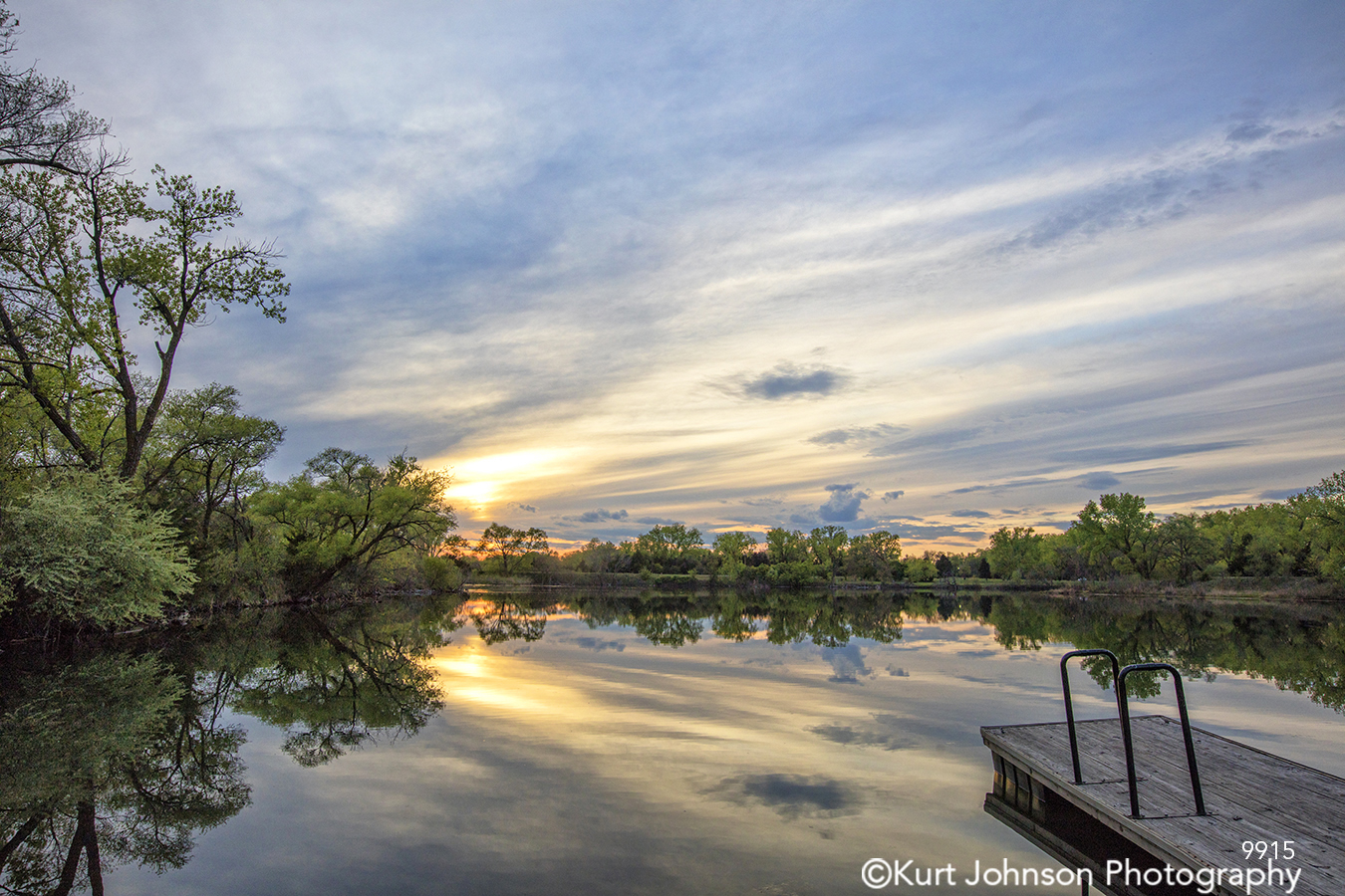 water waterscape sunset green trees blue sky clouds lines texture pattern dock reflection river landscape